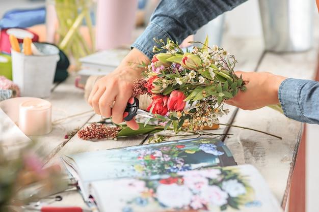 Vrouwelijke handen boeket van verschillende bloemen maken Gratis Foto