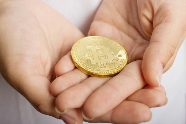 Vrouwelijke handen close-up met de munt bitcoin Premium Foto
