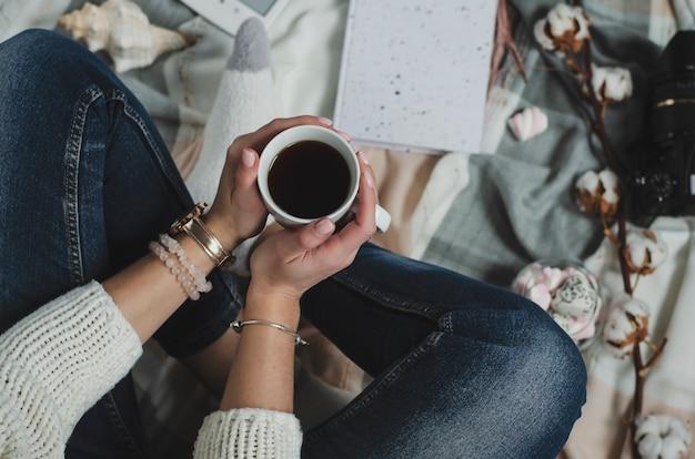 Vrouwelijke handen die een witte mok met drank houden. levensstijl concept. bovenaanzicht Premium Foto