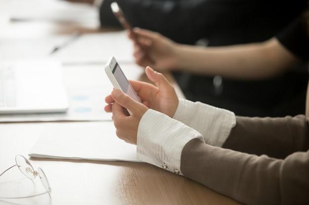 Vrouwelijke handen die mobiele telefoon houden op kantoorvergadering, close-upmening Gratis Foto