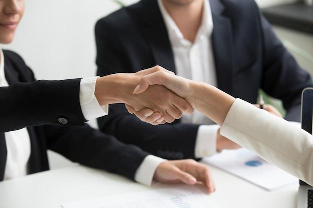Vrouwelijke handen die op groepsvergadering schudden die vennootschapovereenkomst, close-up maken Gratis Foto