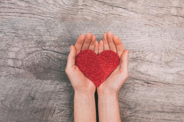 Vrouwelijke handen die rood document hart, op houten achtergrond tonen Premium Foto