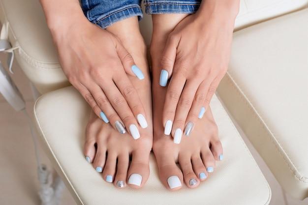 Vrouwelijke handen en voeten met manicure en pedicure nagels, wit, blauw en zilver gel polish Premium Foto