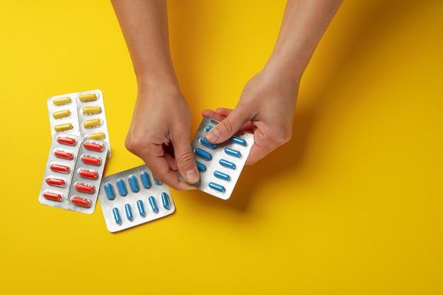 Vrouwelijke handen houden blisterverpakking met pillen geïsoleerd Premium Foto