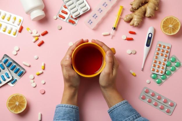 Vrouwelijke handen houden kopje thee met verschillende medicijnen Premium Foto