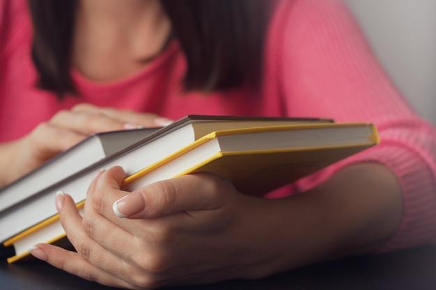 Vrouwelijke handen houden verschillende nieuwe boeken. Premium Foto