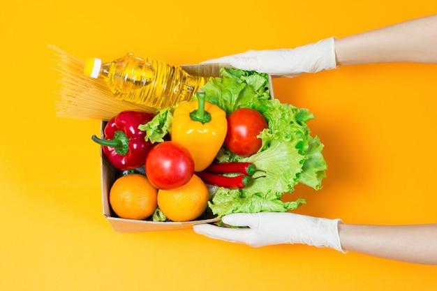 Vrouwelijke handen in medische handschoenen houden een kartonnen doos met voedsel, zonnebloemolie, peper, chili, sinaasappels, tomaten, pasta, geïsoleerd over een oranje ruimte Premium Foto