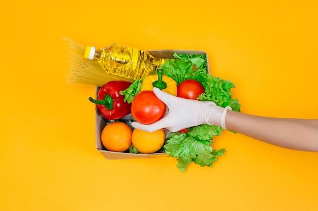 Vrouwelijke handen in medische handschoenen houden een tomaat boven een kartonnen doos met voedsel, olie, peper, chili, sinaasappels, tomaten, pasta, geïsoleerd over een oranje ruimte Premium Foto