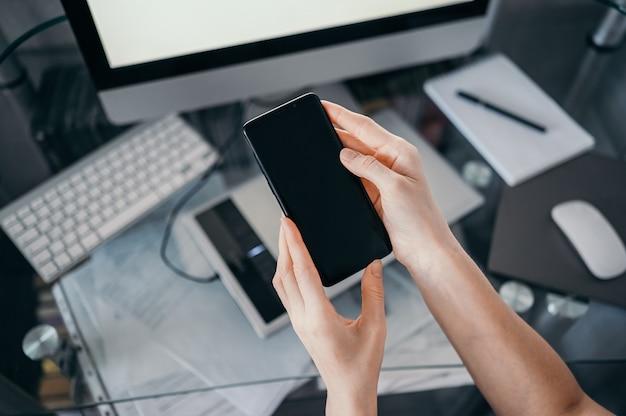 Vrouwelijke handen met behulp van slimme telefoon in interieur werkplek, freelance zakenvrouw met behulp van mobiele telefoon op kantoor, werken vanuit huis met behulp van slimme telefoon en notebook computer. quarantaine op afstand Premium Foto