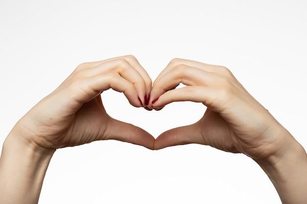 Vrouwelijke handen met een hartvorm-teken Gratis Foto