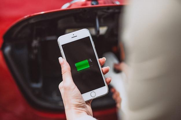 Vrouwelijke handen met mobiele batterij die elektroauto laadt Gratis Foto
