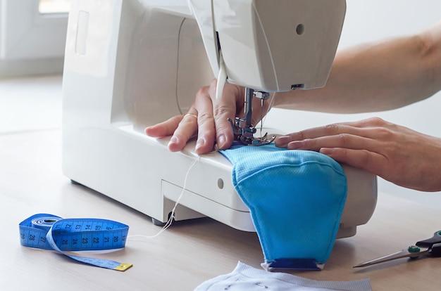Vrouwelijke handen naaien een medisch gezichtsmasker tijdens de quarantaineperiode Premium Foto
