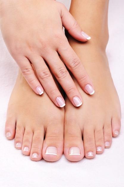 Vrouwelijke handen op de goed verzorgde voeten met franse pedicure Gratis Foto