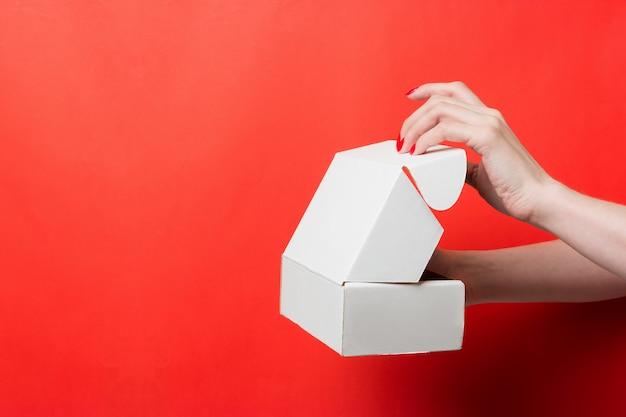 Vrouwelijke handen open witte doos op rode achtergrond Premium Foto