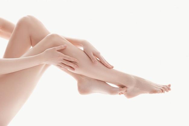 Vrouwelijke handen over de benen, huid lichaamsverzorging concept Gratis Foto