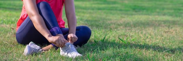 Vrouwelijke handen passen haar loopschoenen aan voor de training. Premium Foto
