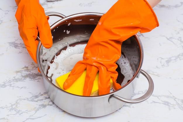 Vrouwelijke handen schuimen de pan met een spons voor het afwassen op de tafel Premium Foto