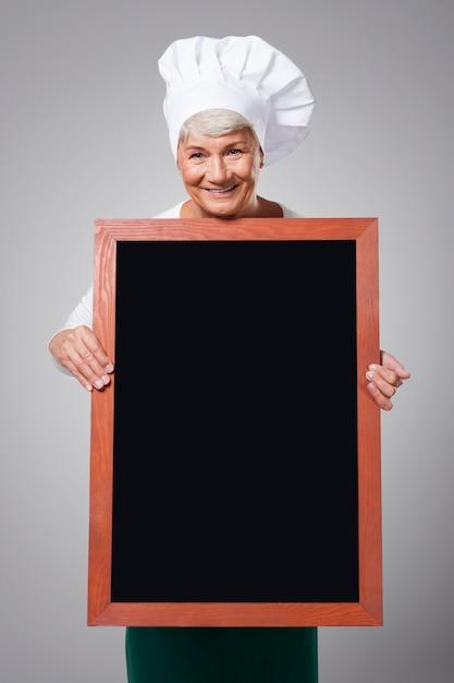 Vrouwelijke hogere chef-kok met menu Gratis Foto