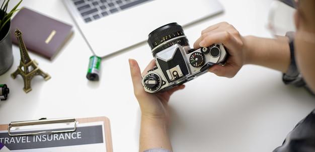 Vrouwelijke holdingscamera terwijl het voorbereiden van reispunten op witte lijst met laptop en reisverzekeringsvorm Premium Foto