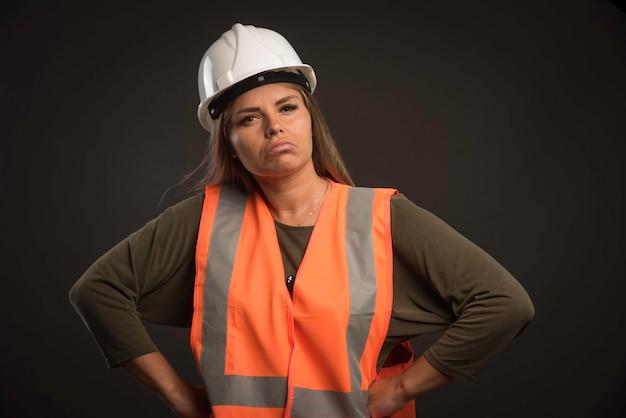 Vrouwelijke ingenieur die een witte helm en uitrusting draagt en er zelfverzekerd uitziet. Gratis Foto
