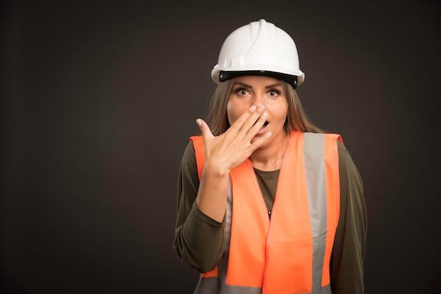 Vrouwelijke ingenieur die een witte helm en uitrusting draagt en kijkt verbaasd. Gratis Foto
