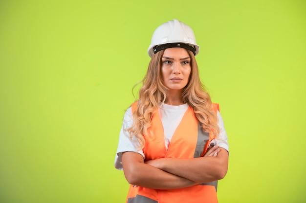 Vrouwelijke ingenieur die verantwoordelijk is in witte helm en uitrusting ziet er depressief uit. Gratis Foto