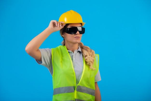 Vrouwelijke ingenieur in gele helm en uitrusting die preventieve straalbrillen draagt en zich zelfverzekerd voelt. Gratis Foto