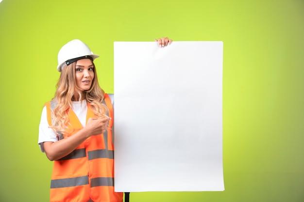 Vrouwelijke ingenieur in witte helm en uitrusting die het bouwplan toont en het uitlegt. Gratis Foto