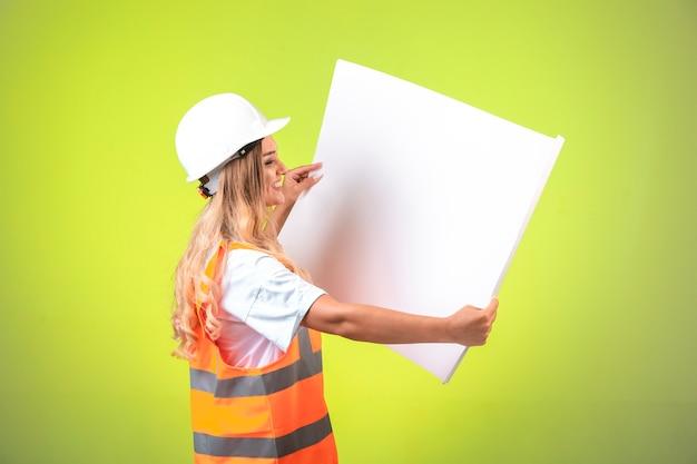 Vrouwelijke ingenieur in witte helm en versnelling projectplan lezen. Gratis Foto