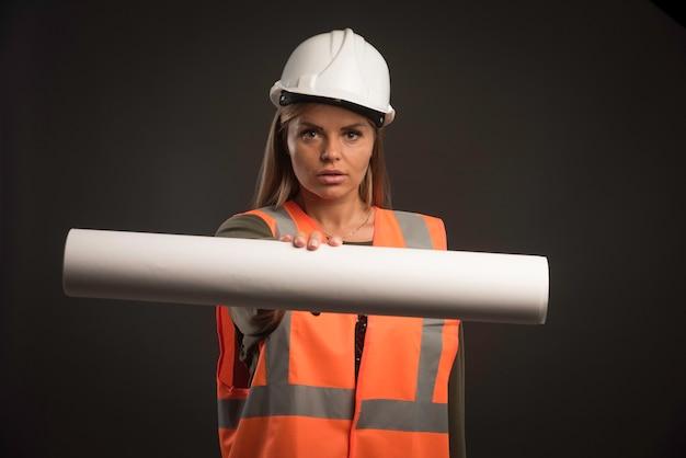 Vrouwelijke ingenieur met een witte helm die het projectplan aanbiedt. Gratis Foto