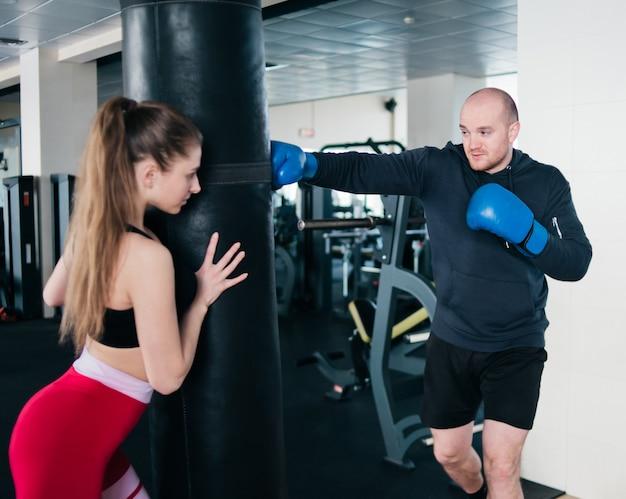 Vrouwelijke instructeur houdt een bokszak en traint een bokser man. jong koppel opleiding Premium Foto