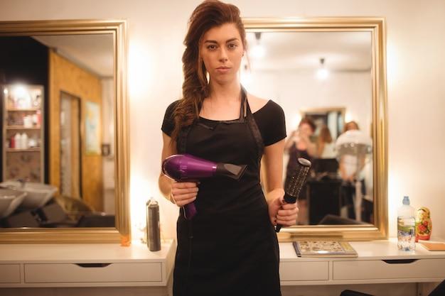 Vrouwelijke kapper houden haardroger machine en haarborstel Gratis Foto