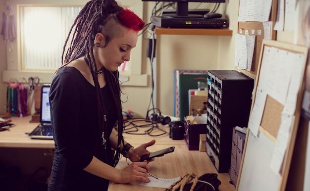 Vrouwelijke kapper met behulp van mobiele telefoon Gratis Foto