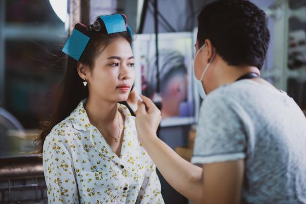 Vrouwelijke kapper permanent, gezicht make-up en het maken van kapsel tot schattige mooie jonge vrouw in schoonheidssalon Gratis Foto