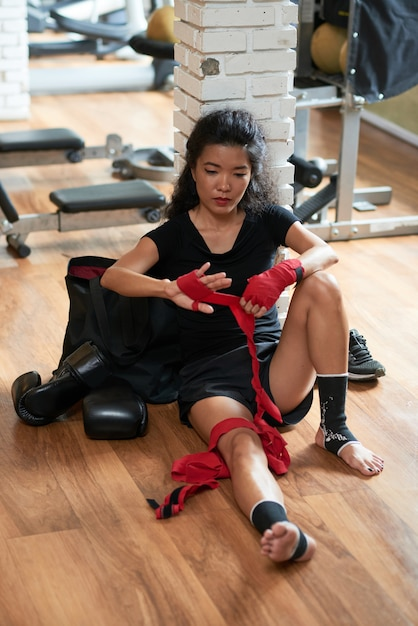 Vrouwelijke kickboxerzitting op de vloer na de gevechtsklasse Gratis Foto