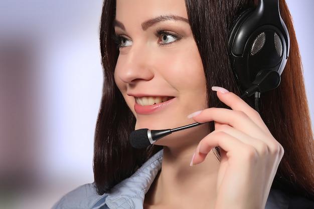 Vrouwelijke klantenondersteuningsexploitant met hoofdtelefoon en het glimlachen Premium Foto