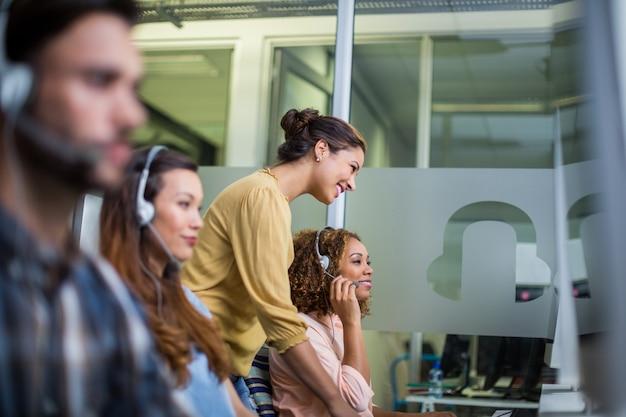 Vrouwelijke klantenservice uitvoerende interactie met haar collega aan balie Premium Foto