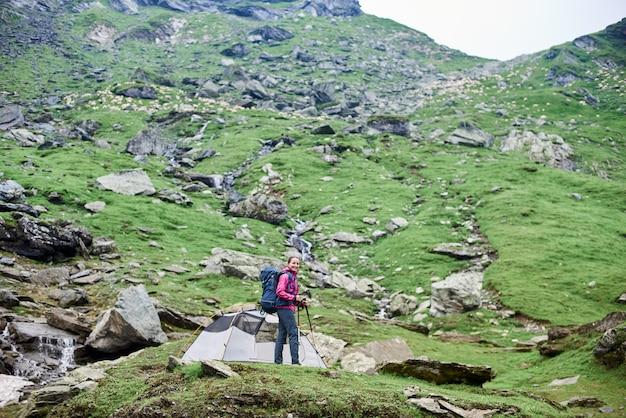 Vrouwelijke klimmer die aan de camera kijkt, die zich op rots dichtbij tent op groene rotsachtige helling in bergen bevindt Premium Foto