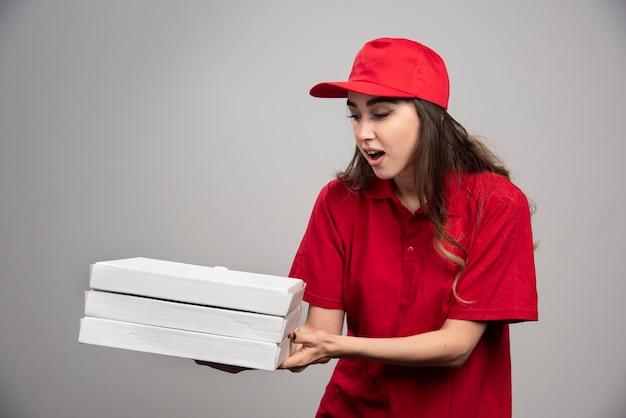Vrouwelijke koerier aangrijpende pizzadozen op grijze muur. Gratis Foto