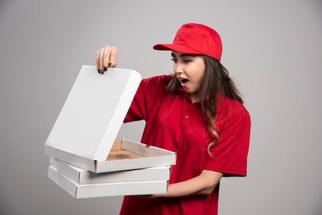 Vrouwelijke koerier die lege pizzadoos bekijkt. Gratis Foto