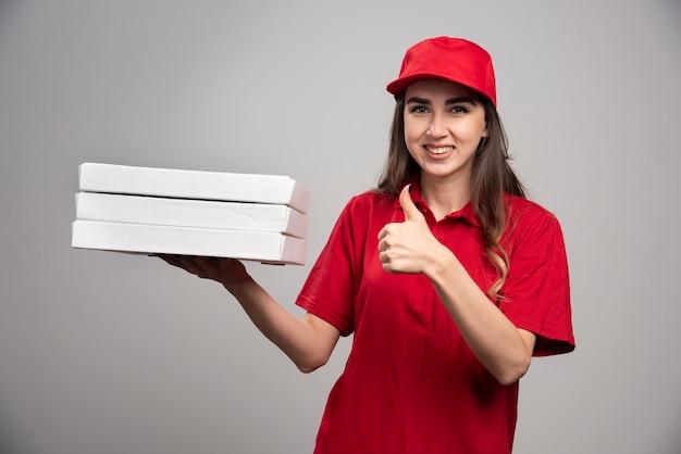 Vrouwelijke koerier pizzadozen houden en duimen opgevend. Gratis Foto