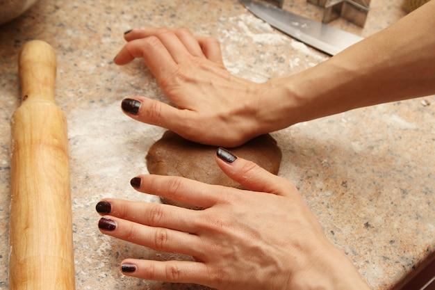 Vrouwelijke kok die het deeg voorbereidt om koekjes in een keuken te maken Gratis Foto