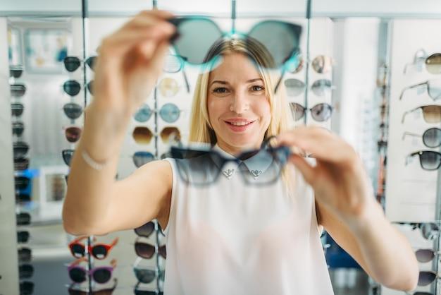 Vrouwelijke koper kiest zonnebril in optica winkel Premium Foto
