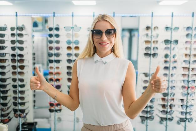 Vrouwelijke koper probeert zonnebril in optica winkel, showcase met bril. ogenbescherming tegen zonlicht in glazenwinkel, oogzorgconcept Premium Foto