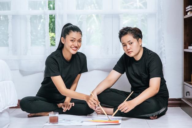 Vrouwelijke koppels tekenen en schilderen op papier. Gratis Foto