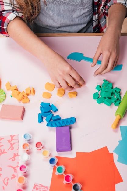 Vrouwelijke kunstenaar die kleurrijk kleistuk over bureau houdt Gratis Foto
