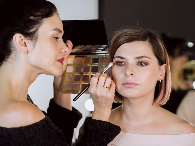 Vrouwelijke kunstenaar die make-up op model toepast Gratis Foto