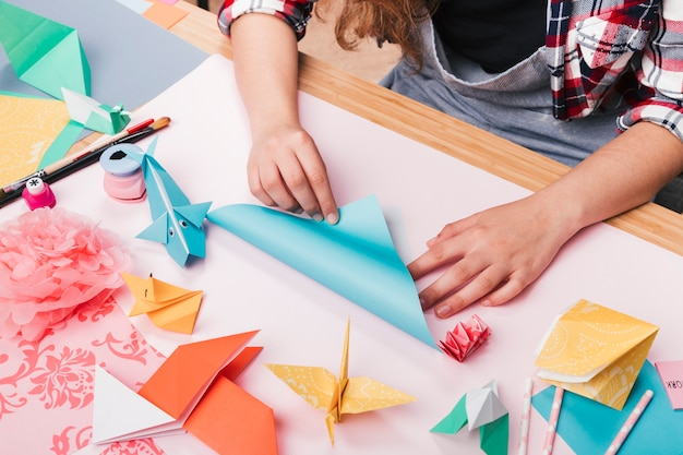 Vrouwelijke kunstenaar die origamidocument vouwt voor het maken van mooie ambacht Gratis Foto