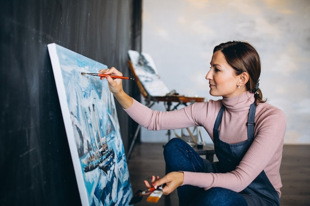 Vrouwelijke kunstenaar schilderij in studio Gratis Foto