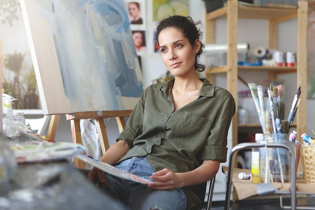 Vrouwelijke kunstliefhebber maakt voorlopige schetsen en probeert zich haar toekomstige meesterwerk voor te stellen, met een doordachte uitdrukking omringd door kunstreproducties. Gratis Foto